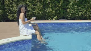 Sensual brunette with cocktail splashes water sitting near swimming pool