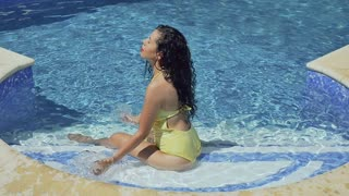 Sensual young girl splashes water on herself sitting in swimming pool