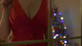 Sexy woman in red dress with open decollete knocking on the window