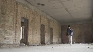 Sick homeless searches something in abandoned building