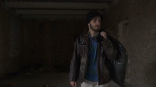 Sick homeless with garbage bag walks in abandoned building in search of food