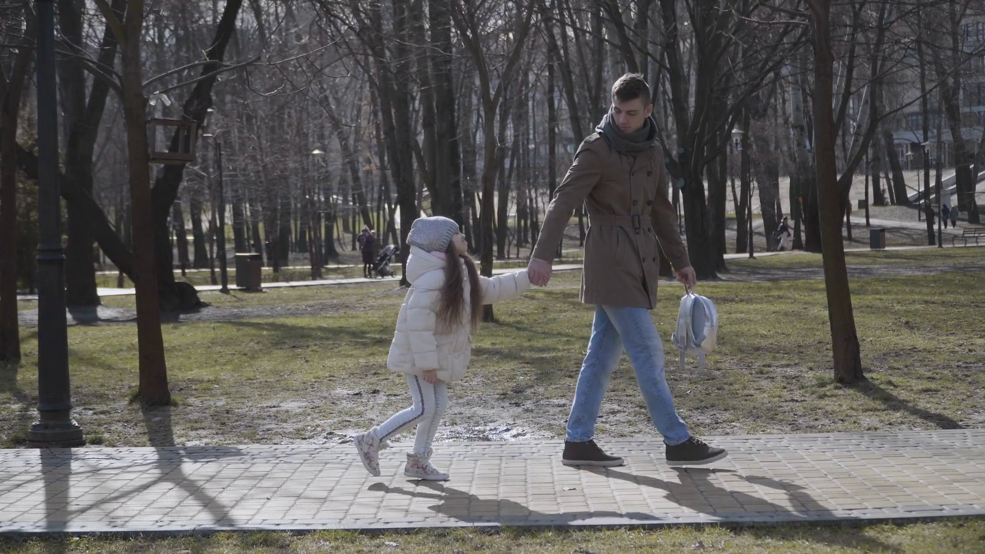 Side view of young Caucasian father(父) forcing little daughter(娘) to go to school. Unwilling cute (女子校生)schoolgirl walking to school with father(父) passing autumn or spring park. Lifestyle, studies, family. Stock Video Footage - Storyblocks