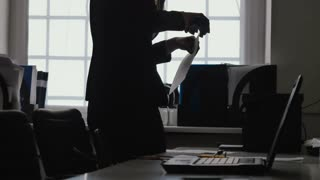 Silhouette of businesswoman staple documents with a stapler in office