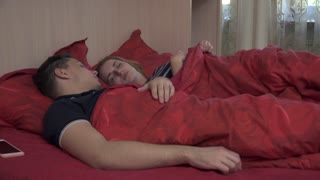 Sleeping young couple in the bedroom