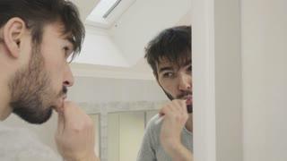 Sleepy guy clean teeth in front of mirror