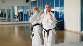 Slowmotion woman's karate trick near the mirror in the gym