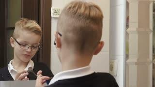 Smart boy imitates shaving on his face