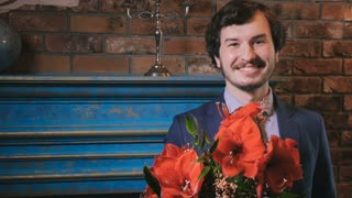Smiling bearded guy with bouquet of red flowers