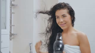 Smiling brunette dries hair with hairdryer in front of mirror