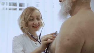 Smiling doctor listen heart of eldelry man with stethoscope