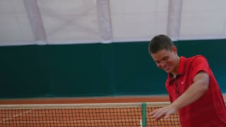 Smiling guy hits the balls on the tennis court