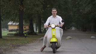 Smiling guy riding a scooter