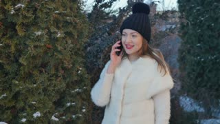 Smiling young girl is talking on phone near a fir-trees