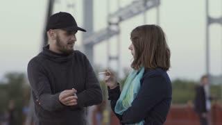 Smoking girl talks with friend on the bridge