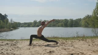 Sportive man stretches the body on the coast of river