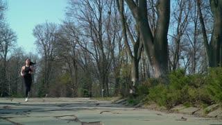 Sports brunette runs in morning park