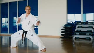 Sporty blonde woman showing some karate tricks in the gym
