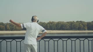 Sporty elderly man makes exercises near the river