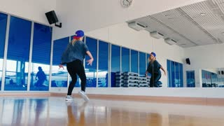 Sporty girl in cap dancing in front of mirror in gym
