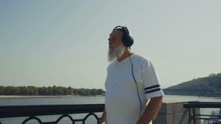 Sporty old man runs near the river