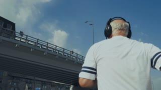 Sporty old man runs under the bridge