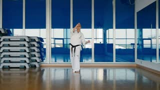 Sporty woman in white kimono practicing the karate tricks in the gym