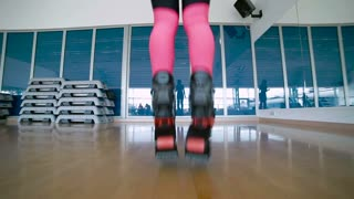 Sporty woman jumps with kangoo shoes in dance studio