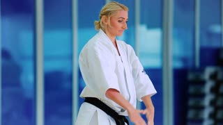 Sporty woman shows a karate trick with hands in the gym