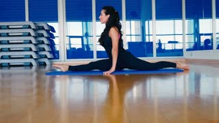 Sporty woman stretching her body in side split and leans to the leg on the mat