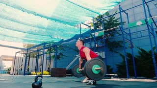 Strong man training with barbell on the sports ground