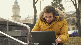 Student uses laptop in park