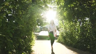 Stylish and confident young woman walking in sunny park in slow motion