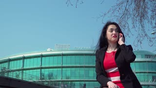 Stylish businesswoman in red dress talk on phone at business center background