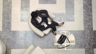 Stylish businesswoman sits in a hotel lobby hall
