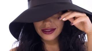 Stylish caucasian brunette in sun-hat at white background
