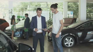 Stylish guy discussing conditions of buying car with salesman in car dealership