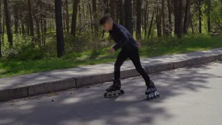 Stylish teenager in leather jacket riding on roller skates in summer park