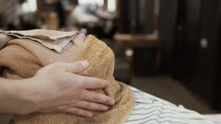 Stylist covers face of mature man with hot towel before shaving