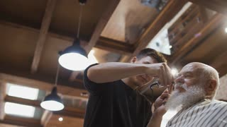 Stylist cuts gray-haired senior man in barbershop