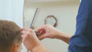 Stylist cuts hair with scissors