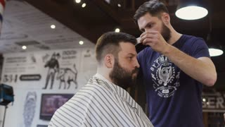 Stylist cuts male hair with scissors and comb in barbershop