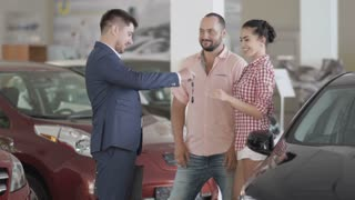 Successful deal between car salesman and young couple in car dealership