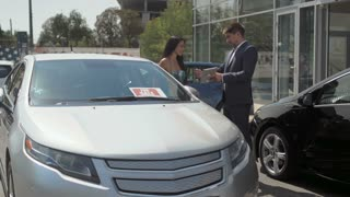 Successful deal of buying automobile in the car showroom outdoors