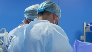 Surgeons make operation in blue operating room