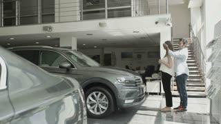 Swarthy guy make a car gift to his girlfriend in car showroom