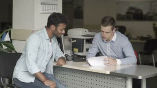 Swarthy guy signs a documents about buying a car in car showroom