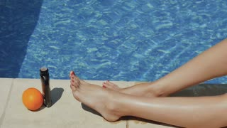 Tanned slim woman legs near a blue pool
