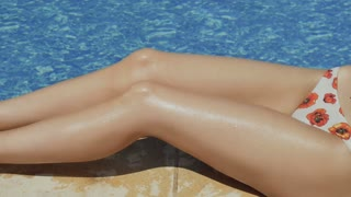 Tanned slim woman legs near swimming pool