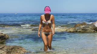Tanned woman in bikini comes out from the sea