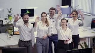 Team of businesspeople waves hands to camera